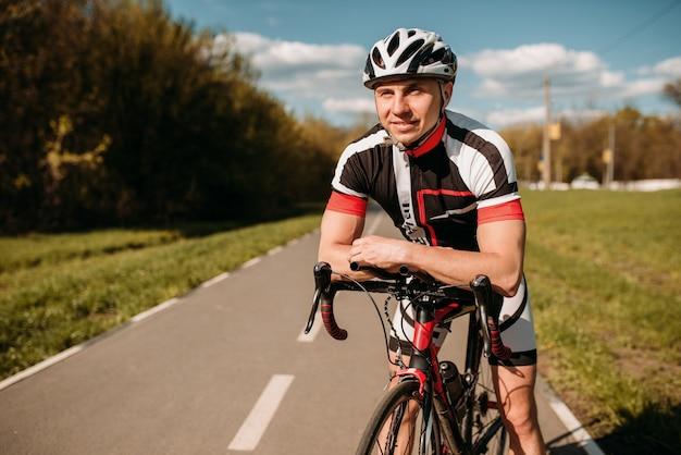 Ciclista em roupas esportivas, pedalando em estrada de asfalto