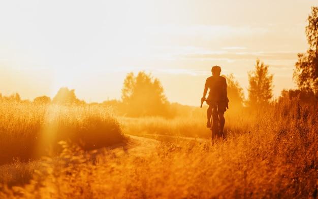 Ciclista em uma bicicleta de cascalho andando em uma trilha empoeirada em um campo ao pôr do sol.