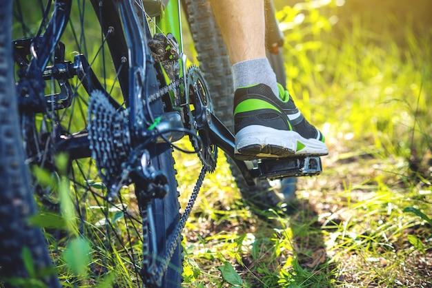 Ciclista em uma bicicleta de montanha verde nas madeiras que montam na grama. o conceito de estilo de vida ativo e extremo