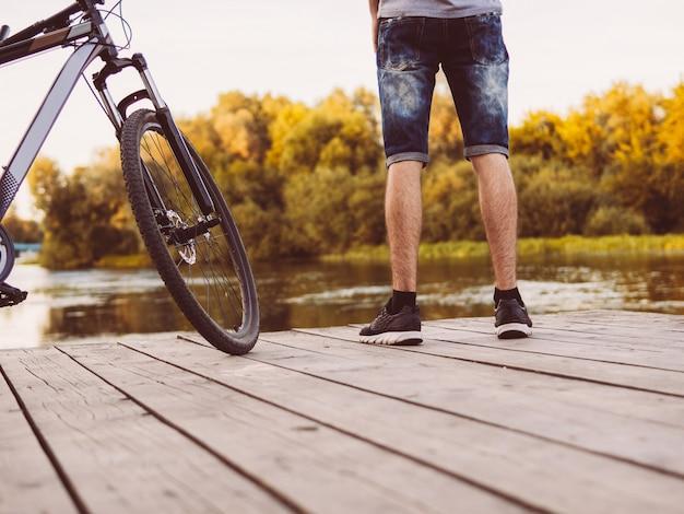 Ciclista em uma ponte de madeira e nos últimos dias do verão