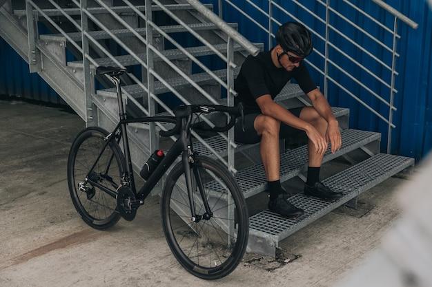 Ciclista exausto sentado em uma escada de metal perto de uma bicicleta ao ar livre