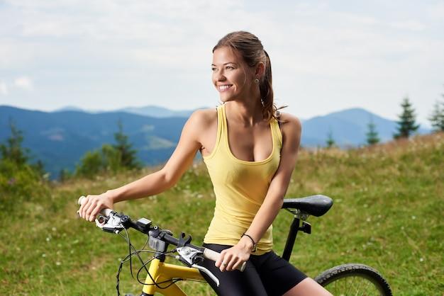 Ciclista femela pedalando em mountain bike amarela