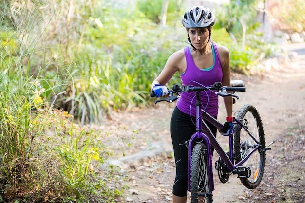 Ciclista feminina carregando bicicleta de montanha enquanto caminhava