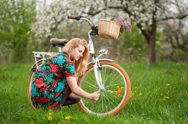 Ciclista feminina com bicicleta branca vintage no jardim primavera
