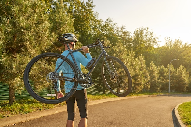 Ciclista forte e atlético em roupas esportivas e capacete protetor carregando sua bicicleta após o treino em