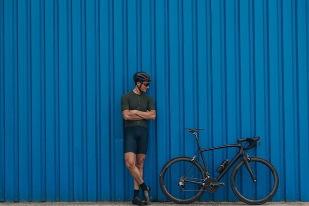 Ciclista forte em pé com a bicicleta perto da parede azul ao ar livre