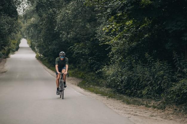 Ciclista forte usando bicicleta preta para treinar ao ar livre