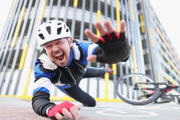 Ciclista gritando caindo da bicicleta no asfalto