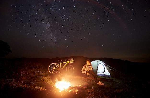 Ciclista jovem desfrutando à noite acampar perto de fogueira em chamas