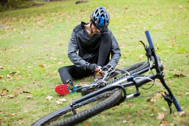 Ciclista masculina amarrar cadarços no parque