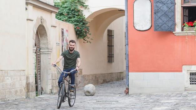 Ciclista masculina andando de bicicleta no pavimento de pedra