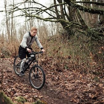 Ciclista masculina andando na trilha da floresta