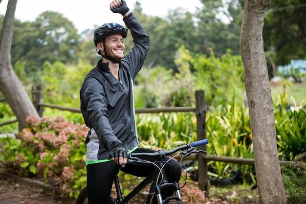 Ciclista masculina em pé com bicicleta de montanha no parque