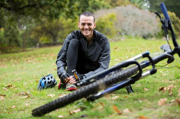 Ciclista masculina relaxante no parque com bicicleta de montanha