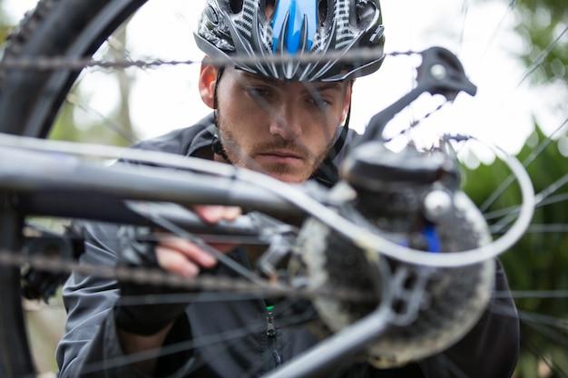 Ciclista masculina, reparando sua bicicleta de montanha