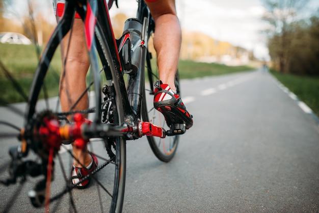 Ciclista masculino anda na ciclovia, vista da roda traseira.
