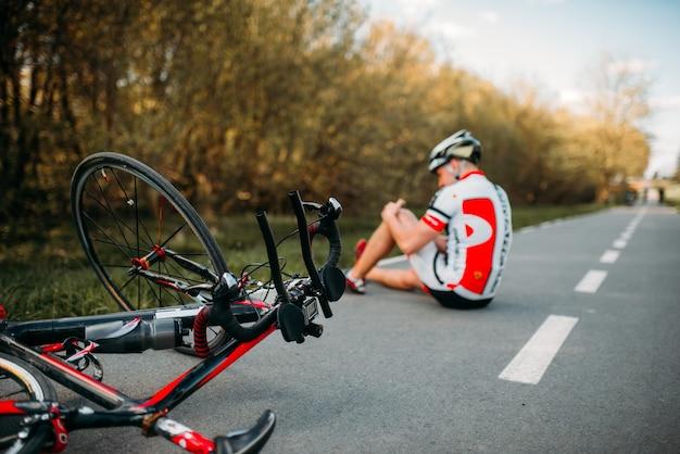 Ciclista masculino caiu da bicicleta e bateu no joelho