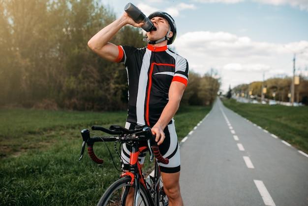 Ciclista masculino de capacete e roupas esportivas bebe água durante o treinamento.