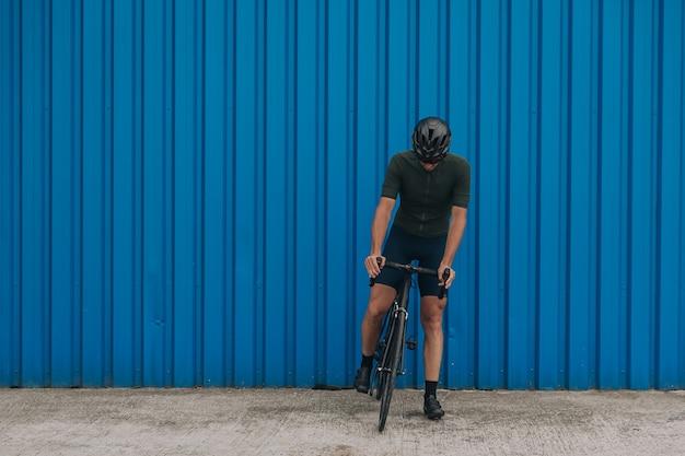 Ciclista musculoso posando com bicicleta esportiva preta perto da parede azul