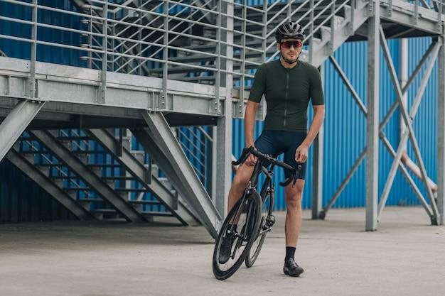 Ciclista musculoso sentado em uma bicicleta sobre uma parede azul com escadas