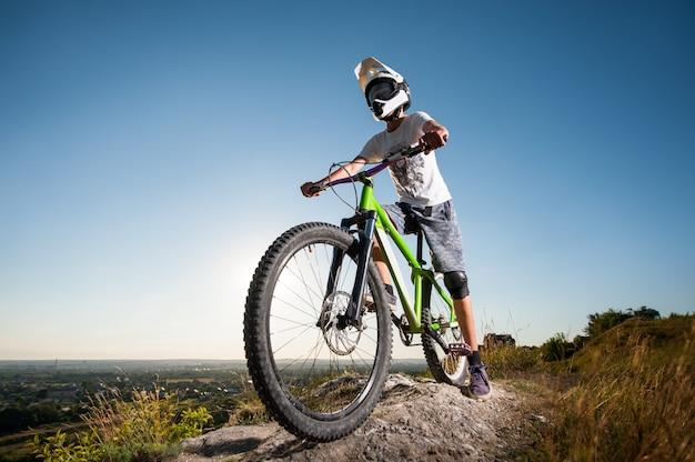 Ciclista no capacete e óculos ficar na bicicleta de montanha