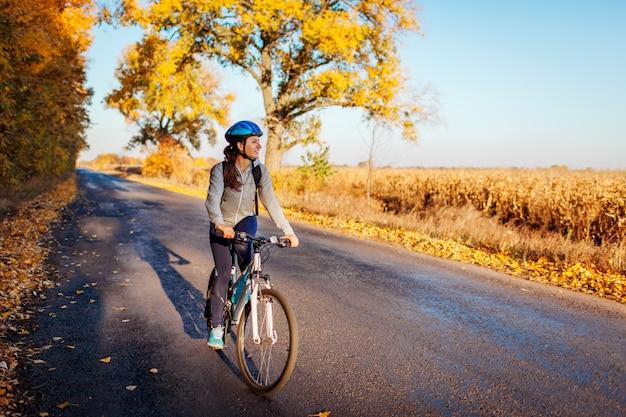 Ciclista nova que monta na estrada do campo do outono no por do sol, mulher feliz que viaja