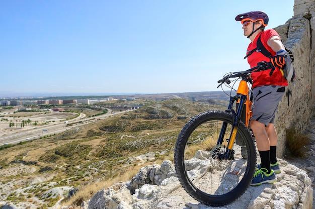 Ciclista olhando da montanha para a cidade
