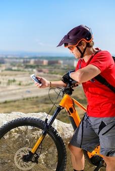 Ciclista olhando para o celular na cidade
