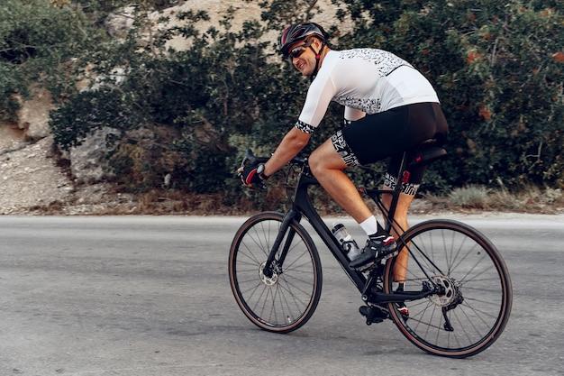 Ciclista pedalando em uma bicicleta de estrada ao ar livre sob o pôr do sol na estrada costeira