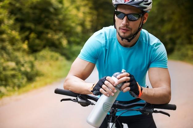 Ciclista pensativo em pé na estrada