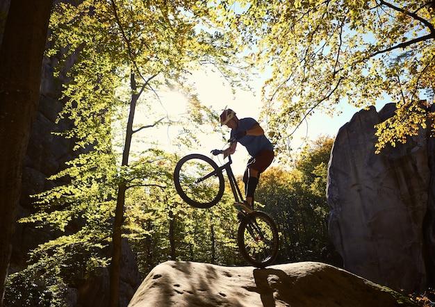 Ciclista profissional equilibrando-se em uma bicicleta experimental ao pôr do sol
