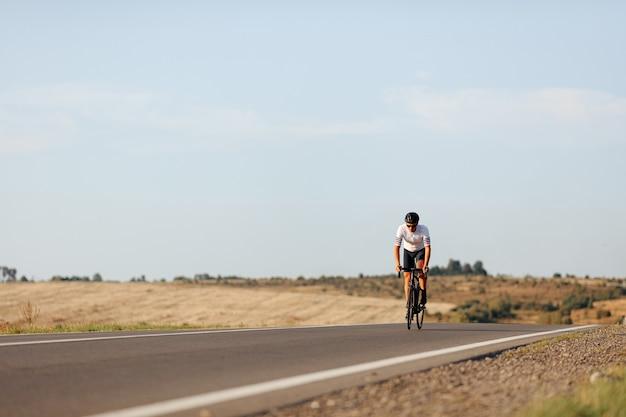 Ciclista profissional forte com capacete preto e óculos, fazendo corridas de longa distância em estrada de asfalto
