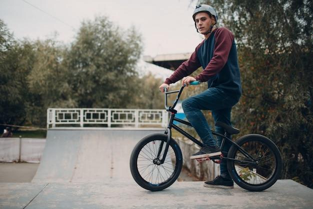 Ciclista profissional jovem esportista masculino com bicicleta bmx no skatepark