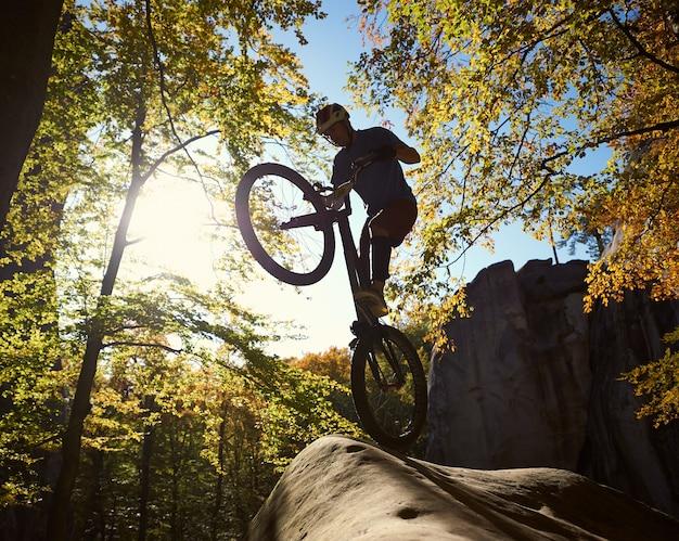 Ciclista profissional se equilibrando em uma bicicleta experimental ao pôr do sol