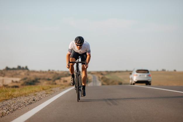 Ciclista profissional usando capacete de proteção e óculos, correndo na estrada de asfalto durante um dia ensolarado