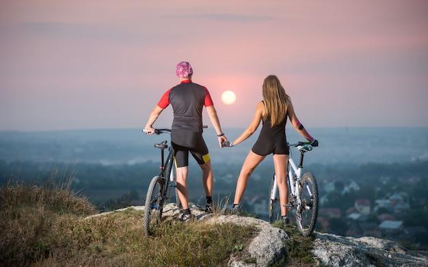 Ciclista romântica com bicicletas de montanha em pé no topo de uma colina