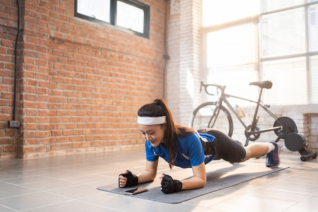 Ciclista se exercitando com sua pose de prancha em casa ela usa um telefone com timer