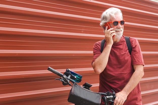 Ciclista sênior em excursão urbana com bicicleta elétrica usando telefone celular sorrindo
