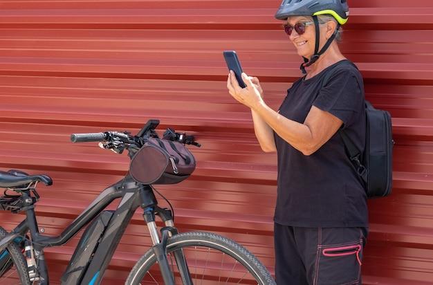 Ciclista sênior sorridente em uma cidade urbana ao ar livre usando telefone celular e desfrutando de um estilo de vida saudável