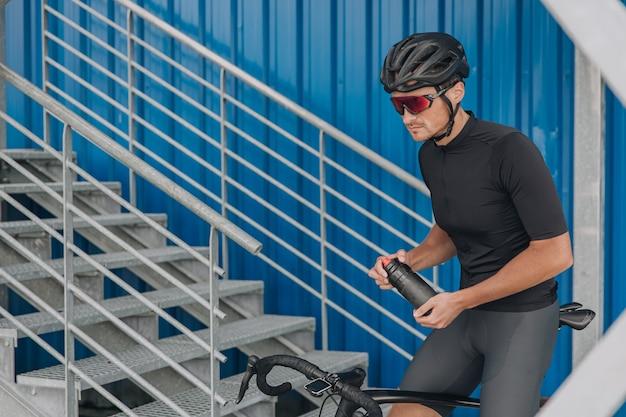 Ciclista sentado em uma bicicleta segurando uma garrafa de água
