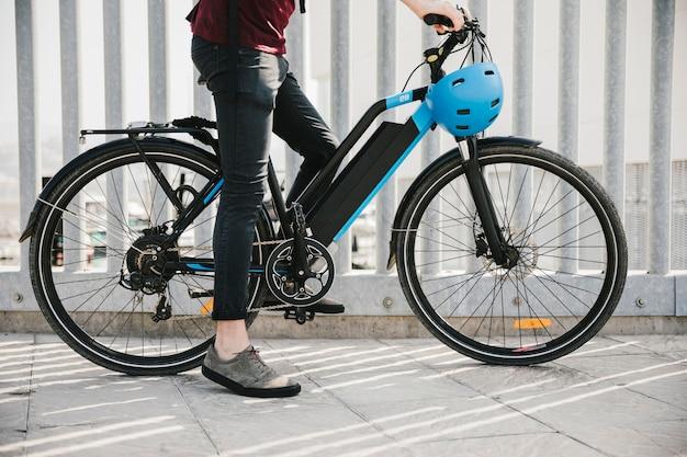 Ciclista urbana, tendo um freio na e-bicicleta