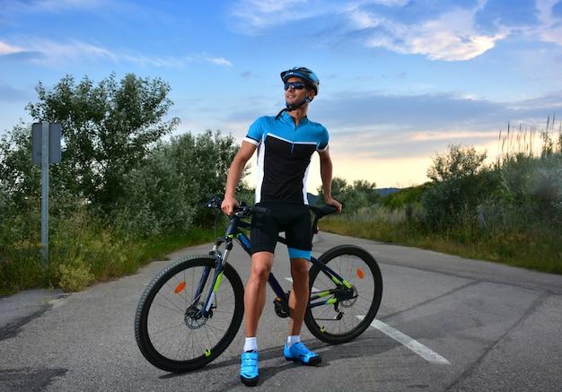 Ciclista vai de bicicleta de montanha ao longo de uma estrada solitária
