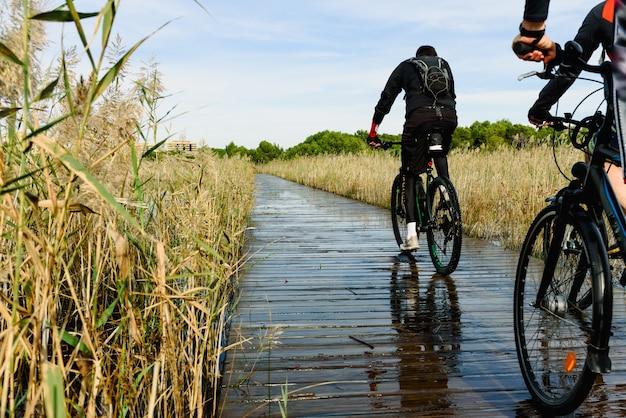 Ciclistas atravessando uma passarela sobre um lago inundado em valência, espanha, em um dia ensolarado