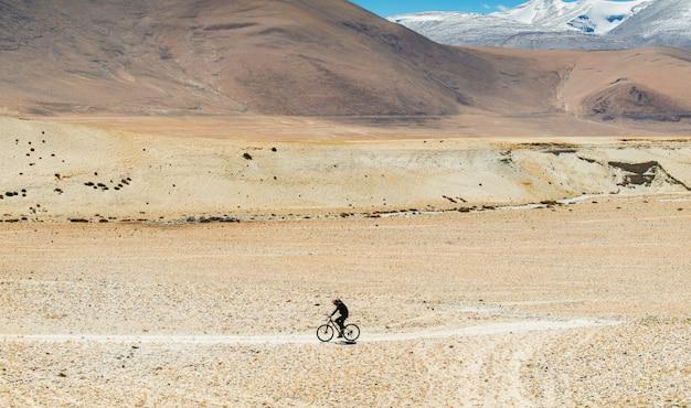 Ciclistas de homens através da estrada acidentada na cordilheira do himalaia