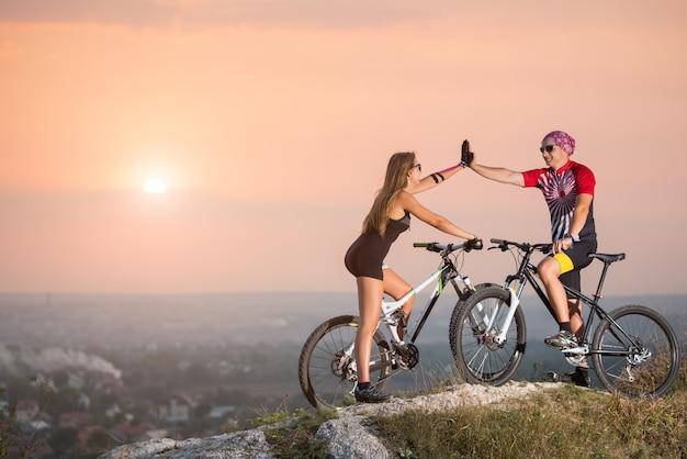Ciclistas de montanha dando uns cinco para o outro