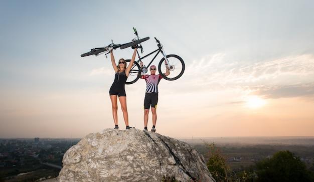 Ciclistas na rocha e levantaram suas bicicletas