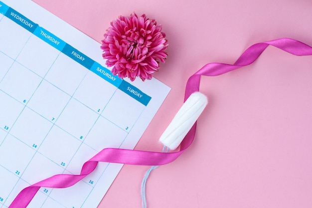 Ciclo menstrual regular. tampões, calendário feminino, flores. cuidados de higiene em dias críticos. cuidados de saúde femininos e ginecológicos.