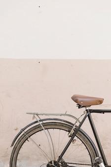 Ciclo velho estacionado perto de muro de concreto