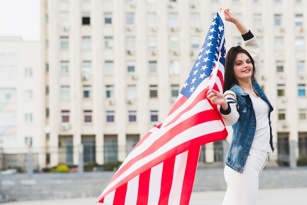 Cidadão americano feminino orgulhoso com bandeira desdobrada