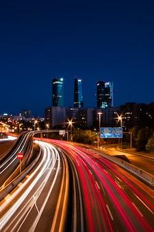 Cidade à noite com trilhas de trânsito